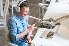 Jubilant guy listening to music. Like a real drummer. Cheerful delighted handsome guy sitting at the table a pretending to drum while listening to music Royalty Free Stock Photos