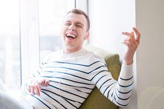 Jubilant guy listening to music. Switch your imagination. Positive emotional guy sitting on the window sill and listening to music while pretending to play the Stock Images
