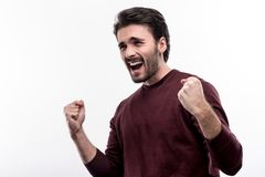 Jubilant man screaming joyfully and clenching fists in triumph. Amazing mood. Charming bristled young man clenching his fists and raising the arms in triumph Stock Photography