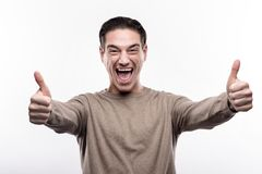 Jubilant middle-aged man showing thumbs up royalty free stock images