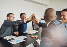 Jubilant multiracial business team cheering. And laughing as they congratulate each other with a high fives hand gesture Stock Photos