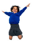 Jubilant school kid jumping high up in the air. Excited jubilant school kid jumping high up in the air after hearing her annual result Royalty Free Stock Photo