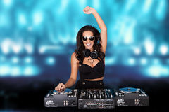 Jubilant female disc jockey. Standing behind her mixing deck laughing and holding up her hand against a backdrop of blue party lights with copyspace Royalty Free Stock Photos