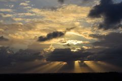 Jubilant skyscape with series of sun rays breaking through over land. Joyous sun beams stretch across expansive sky and horizon. Image evokes a sense of triumph Royalty Free Stock Photography