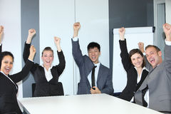 Jubilant successful business team. Of motivated multiethnic young people sitting celebrating and cheering at a table in the office with broad smiles Stock Photos