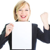 Jubilant woman with blank sheet of paper. Smiling and raising her fist in celebration isolated on white Royalty Free Stock Images