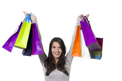 Jubilant woman holding aloft shopping bags. Jubilant woman shopper holding aloft a collection of colourful shopping bags with a beaming smile rejoicing in all stock image