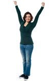 Jubilant woman with raised arms celebrating victory Stock Images