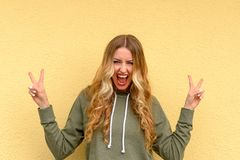 Jubilant woman screaming and making a V-sign. Jubilant attractive blond woman screaming and making a double V-sign with her fingers for peace or victory over a Royalty Free Stock Image