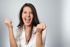 Jubilant young woman cheering her success. Raising her fists in the air in excitement and elation at her achievement or victory Royalty Free Stock Photos