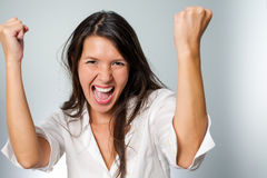 Jubilant young woman cheering her success raising Stock Photos