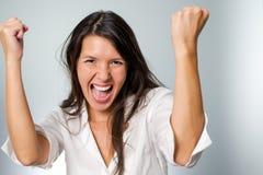 Jubilant young woman cheering her success raising Stock Photos