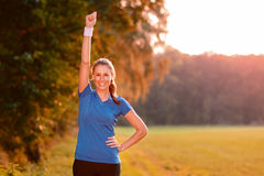 Jubilant young woman punching the air. With her raised fist as she celebrates a success while standing in lush green countryside in early morning light Stock Photos