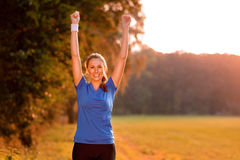 Jubilant young woman punching the air. With her raised fist as she celebrates a success while standing in lush green countryside in early morning light Stock Images