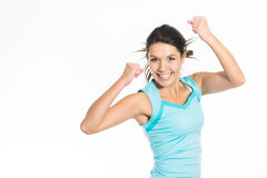 Jubilant young woman rejoicing. Raising her fists in the air with a triumphant smile Royalty Free Stock Photos