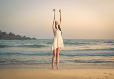 Jubilating女孩在海边 图库摄影