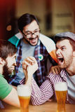 Jubilation. Ecstatic fans expressing their gladness upon victory in pub stock images