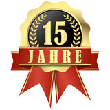 Jubilee button with banner and ribbons for 15 years. (in german Stock Images