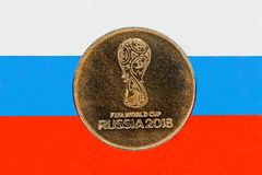 Jubileums- mynt som är hängivet till världscupen i 2018 Mot bakgrunden av den ryska flaggan Royaltyfria Foton