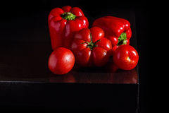 Jucy bell peppers and fresh tomatoes on dark wooden background Royalty Free Stock Images