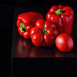 Jucy bell peppers and fresh tomatoes on dark wooden background Stock Photography