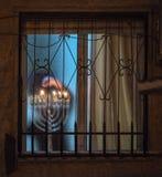 Judeu ortodoxo que ilumina velas do hanukia durante o feriado judaico do chanuka imagens de stock