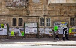 Judeus ultra ortodoxos que andam após o jornal de parede Foto de Stock
