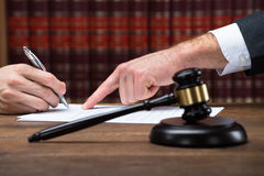Judge Assisting Client To Sign Legal Document In Courtroom Stock Photos