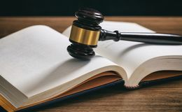Judge or auction gavel on an open book, wooden desk. Law or auction gavel on an open book, wooden desk, dark background Royalty Free Stock Image