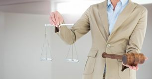Judge with balance scale and hammer in front of window light Stock Photos