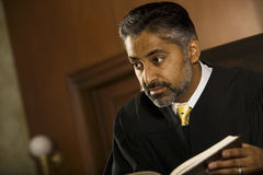 Judge With Book Looking Away In Court Room. Middle age male judge with book looking away in court room royalty free stock images