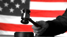 Judge calling order with gavel in american court in selective black and white