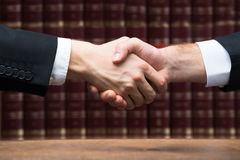 Judge And Client Shaking Hands Against Books Royalty Free Stock Photos