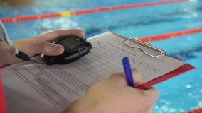Judge at competition in pool. Close-up of the judge`s hand in the pool which records the testimony in the sheet