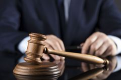 Judge concept. Place for text. Judge signs the documents. Gavel on a glass table. Law and justice theme stock photos
