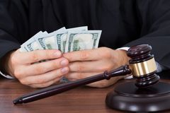 Judge counting banknotes at desk Royalty Free Stock Photography