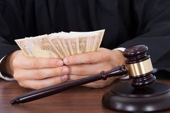 Judge counting money at desk Royalty Free Stock Photography