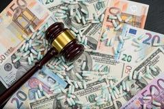 Judge& de madera x27; mazo de s y drogas coloridas dispersadas en el dólar fotografía de archivo libre de regalías