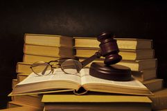 Judge Gavel. Justice gavel and eye glasses on a pile of legal books on a lawyer desk Stock Image