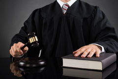 Judge With Gavel And Book. Close-up Of Male Judge With Gavel And Book At Desk Royalty Free Stock Photography