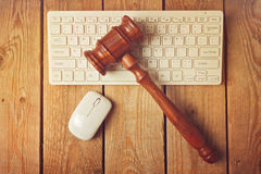 Judge gavel and computer keyboard on wooden vintage background Stock Images
