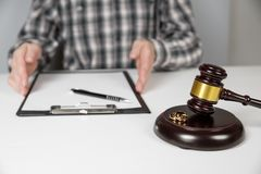 Judge gavel deciding on marriage divorce. Hands of judge, signing decree of divorce, dissolution, canceling marriage, legal separation documents, filing royalty free stock image