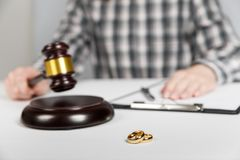 Judge gavel deciding on marriage divorce. Hands of judge, signing decree of divorce, dissolution, canceling marriage, legal separation documents, filing royalty free stock photo