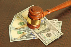 Judge gavel and dollar banknotes on wooden table. Stock Photos