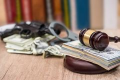 Judge gavel with dollars, books on wooden desk royalty free stock images