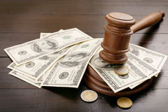 Judge gavel with dollars and euro cents. And on brown lacquered wooden desk close up with copy space. Concept for auction bidding royalty free stock image