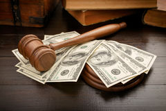 Judge gavel with dollars and law books. On brown lacquered wooden desk close up with copy space Royalty Free Stock Photos