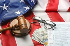 Judge gavel, eyeglasses, money and tax forms. On American flag background Stock Image