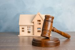 Judge gavel and house model on wooden table. Estate law concept. Judge gavel and house model on table. Estate law concept stock photography