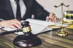 Judge gavel with Justice lawyers, Gavel on wooden table and Counselor or Male lawyer working on a documents at law firm in office. Legal law, advice and stock image